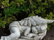 Schlafende Engelfigur liegend in Engelsflügeln. - Uslar